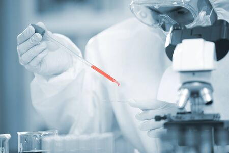 Il medico analizza il tubo di sangue corona o covid-19, sta trovando il vaccino campione in laboratorio e indossa tuta e maschera in dpi per proteggere il virus, maschera medica, ospedale, concetto di epidemia di quarantena