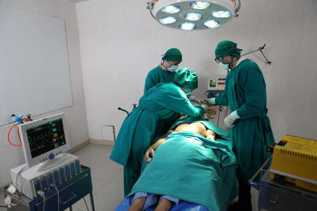 Team of professional surgeons performing operation in hospital , they are holding defibrillator and help while patient will die operation room at hospital