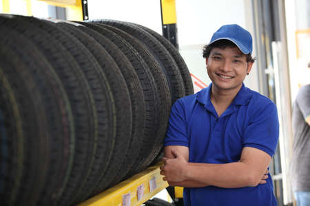 Salesman with showing wheel tires at car repair service or auto store, business, maintenance and people concept 版權商用圖片