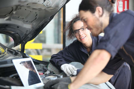 car mechanic use notebook computers to check engine and service maintenance of industrial to engine repair, for transport automobile automotive