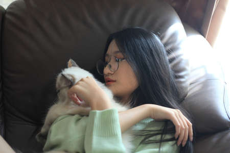 young teen age stay at home and hug a cat 版權商用圖片