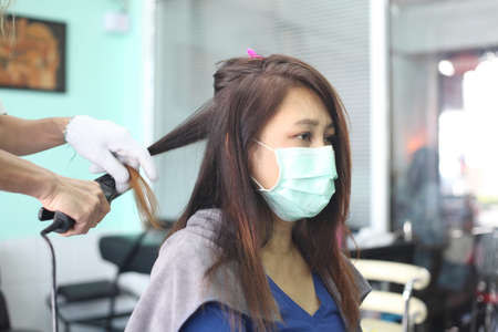woman customer in a salon with medical masks during virus pandemic. Working with safety mask.