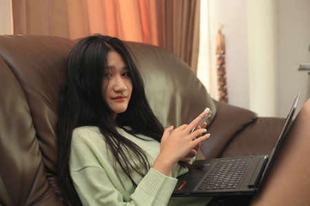 smiling young teen girl sitting on sofa at home with laptop,  making purchases in online store, entering payment confirmation code from mobile phone message, shopping in internet 版權商用圖片