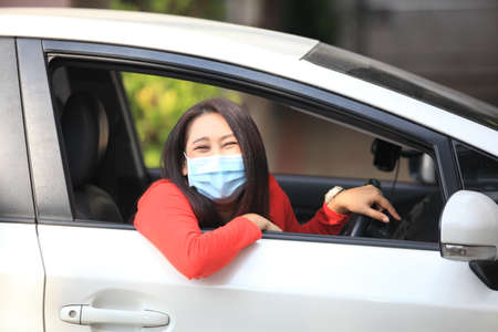 Young woman with medical protective mask on her face is driving a car, she looks into camera and View from outside , Protect yourself. 版權商用圖片