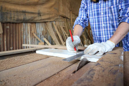 Carpenter, he is working in the workshop. Man at work on wood. Image of mature carpenter in the workshop, furniture making concept. Stock Photo