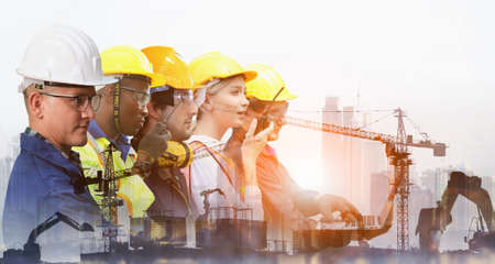 Group of architects and engineers at a building site , Team of expert architects on construciton site in helmets checking workflow
