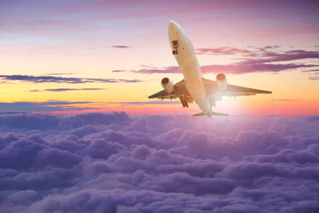 Big white airplane is flying over the clouds with colorful sky at sunset for Business trip with Commercial plane, Transportation, import-export and logistics, Travel concept , Airplane is flying for Business trip, Transportation, import-export, logistics, Travel Stockfoto