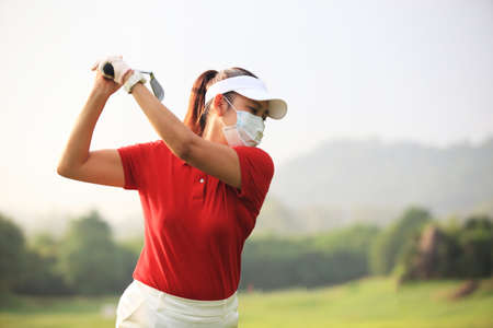 Beautiful golf course at the sunset, sunrise time,female golf player on professional golf course. Golfer with golf club taking a shot