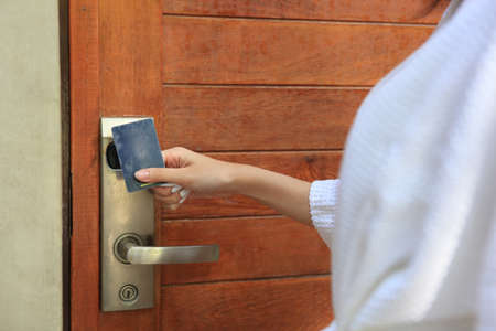woman  open door with keycard , Closeup of female housekeeper's hands holding cardkey and opening door of hotel room Stockfoto