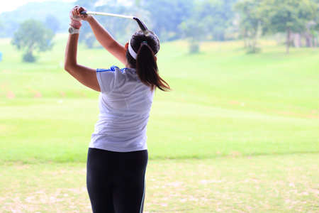 Woman golf player swing shot on course or Girl golf player with driver shoot over lake, view from behind.