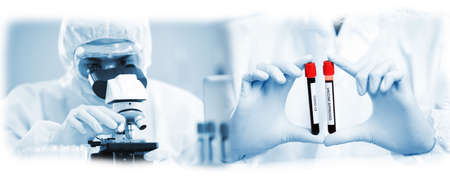 COVID-19, Corona Virus ; scientist  analyzing covid 19 sample with microscope and holding coronavirus covid 19 blood sample tube on hand in laboratory, coronavirus covid 19 vaccine research
