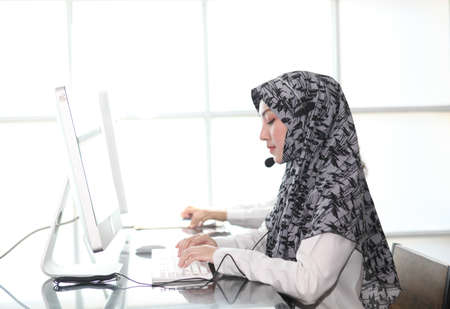 Asian Muslim female  with headsets working in a call centre,Call center agent with headset working on support hotline in modern office. Call center worker accompanied by her team. speaking to partner