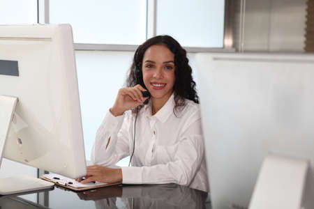 woman agent with headsets working in a call centre,Call center agent with headset working on support hotline in modern office. Call center worker accompanied by her team.