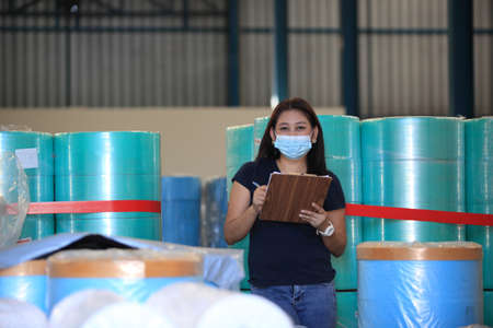 worker woman  with mask on face she are checking stock at  warehouse  ,woman worker with medical mask holding clipboard and checking inventory in the warehouse