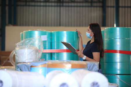 worker woman  with mask on face she are checking stock at  warehouse
