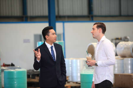Happy business people talking on meeting at factory industry or Mature company manager greeting a worker  in industrial facility or warehouse