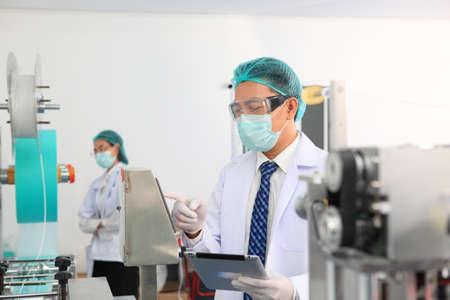 Production engineer with face mask working in factory , Qc engineer checking mask for good quality , Concept of protective action and quarantine to stop spreading of  Disease