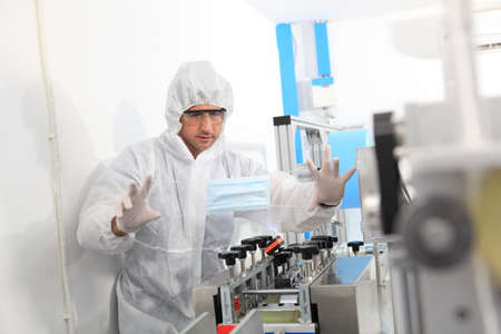 Production engineer with face mask working in factory , Qc engineer checking mask for good quality , Concept of protective action and quarantine to stop spreading of Coronavirus Disease 2019