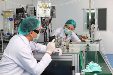 Production engineer with face mask working in factory , Qc engineer checking mask for good quality Stockfoto