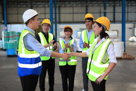 Business people shaking hands, finishing up a meeting ,  wholesale, logistic, people and export concept - manual worker and businessmen with clipboard shaking hands and making deal at warehouse