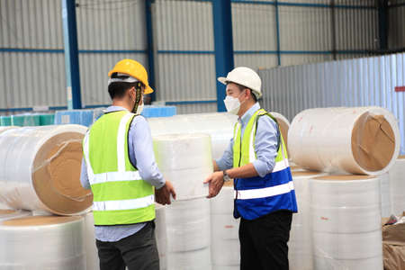 warehouse worker holding cardboard box , shipping workers marking shipping list and carrying cardboard box for delivery in modern warehouse Stockfoto