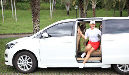 woman travel by car to golf, woman loading a golf bag into the boot of a parked car on the driveway. Stockfoto