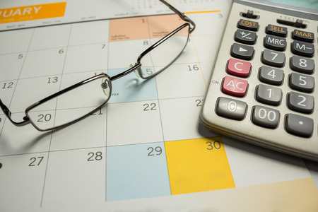 Business concept with calendar and Calculator and eyeglasses