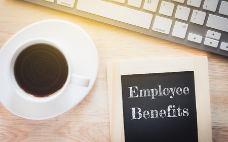 Concept Employee Benefits message on wood boards. A keyboard and a glass coffee table.Vintage tone. Stock Photo
