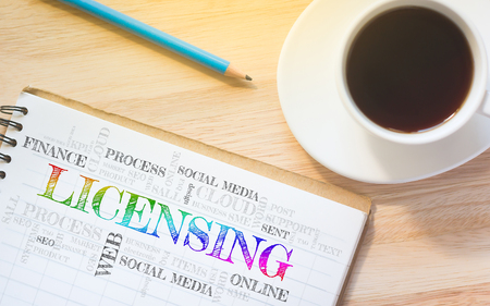 licensing: Concept LICENSING message on book. A pencil and a glass coffee table.Vintage tone. Stock Photo