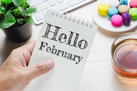 attributed: Man holding Hello February message on book and keyboard with a hot cup of tea, macaroon on the table. Can be attributed to your ad. Stock Photo