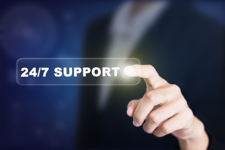 24x7: Businessman pressing a 247 SUPPORT concept button. Can be used in advertising. Stock Photo