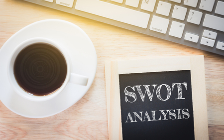 swot: Concept SWOT ANALYSIS message on wood boards. A keyboard and a glass coffee table.Vintage tone. Stock Photo