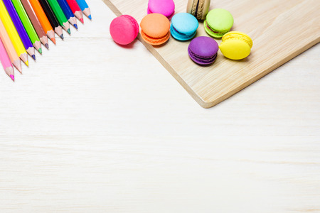 text pink: macaroon placed on a wooden table and a multi-colored pencils. Leave it blank, enter text.