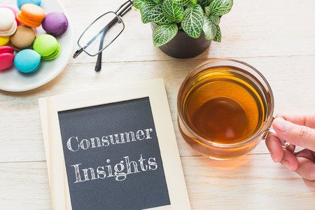 consumer: Concept Consumer Insights message on wood boards. Macaroons and glass Tea on table. Vintage tone.