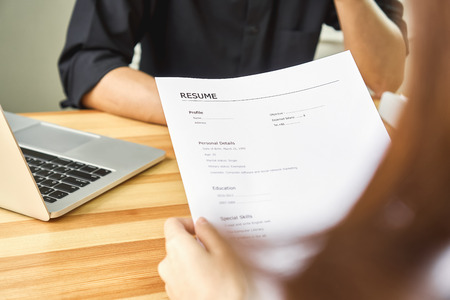 Young woman submit resume to employer to review job application. The concept presents the ability for the company to agree with the position of the job. Stock Photo
