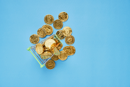 Top view, Gold Bitcoin placed in a small shopping cart. Digital currency concepts can be used to make online purchases. Stock Photo