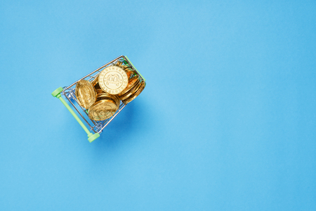 Gold Bitcoin placed in a small shopping cart. Digital currency concepts can be used to make online purchases. Stock Photo