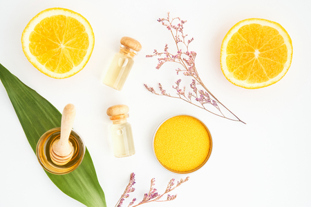 Top view, Bottle of natural oil and orange placed, Blank label package for mockup on white background and flowers. The concept of natural beauty products.