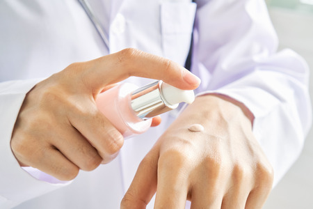 Scientists are using white cream from a bottle to clean his hands. Hygienic concept in hygiene and prevention of germs from the outside.