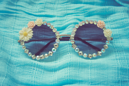 Fashionable eyewear beautifully decorated. Lay on blue fabric floor. Vintage style