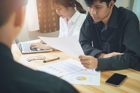The staff is consulting with customers who use their business services. Stock Photo