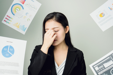 Business woman in a black suit is throw away a lot of paperwork and the documents are blown overhead. showing signs of stress from hard work. The concept of stress from hard work is bad for health.