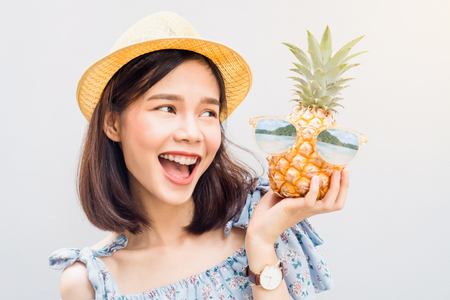 Young girl happy smile and cheerful in blue dress and hold pineapple in hand, Wear sunglasses with a reflection of the beach and island. Concept summer travel.