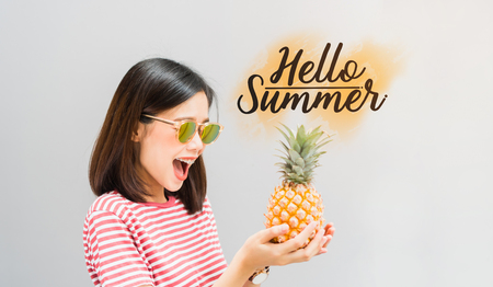 Young girl happy smile and cheerful in red dress and hold pineapple in hand, And have a message Hello Summer. Concept summer travel.