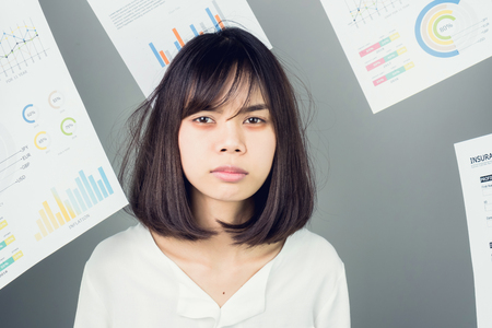 Business woman in a white dress is throw away a lot of paperwork and the documents are blown overhead. showing signs of stress from hard work. The concept of stress from hard work is bad for health.