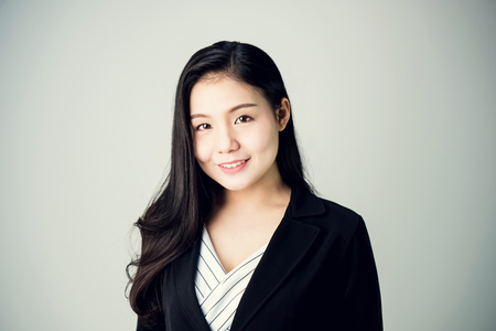 Portrait of business woman in a suit is smiling and looking forward. on a white background.
