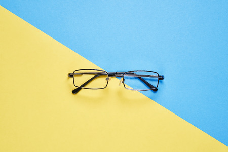 Eyewear placed on a pastel yellow and blue background divides the halves.