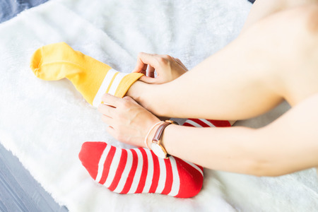 The girl sit on a white carpet and put on socks, yellow punctuate red side. Stock Photo