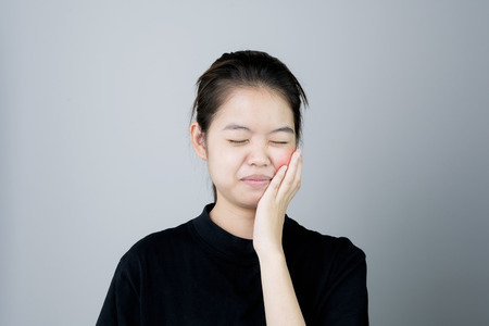 Asian girl in black casual dress Show off the toothache, Maybe because of not maintaining good oral health. on a gray background gives a soft light.
