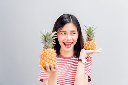 Young girl happy smile and cheerful in red dress and hold two pineapple in hand. Concept summer travel. Stock Photo